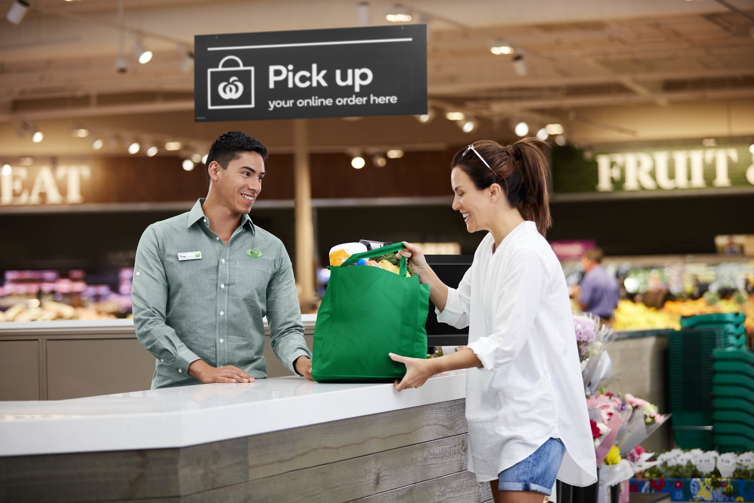 Man serving woman at supermarket