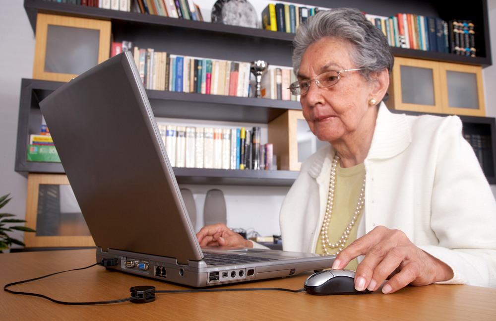 eldery woman on a laptop at home reading the screen